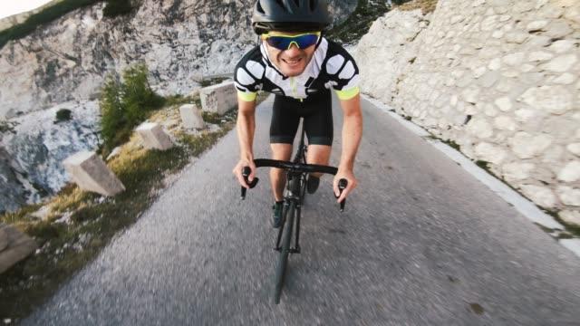 vidéos et rushes de coureur de route mâle gai pédalant en montée dans le flanc de montagne - qui monte