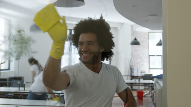 vídeos de stock e filmes b-roll de cheerful man cleaning a window spraying soap and dancing while cleaning it and team cleaning at background - porteiro