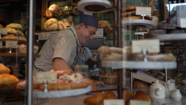 cheerful man cleaning the counter at a bakery while woman is putting on protective gloves to arrange the bread display - cleaning stock videos & royalty-free footage