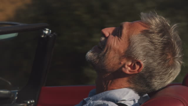 cheerful man driving vintage car during windy day - vintage car stock videos & royalty-free footage