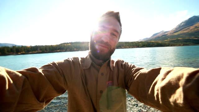 Glad man i naturen tar selfie stående nära lake