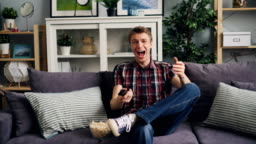 Cheerful man is watching funny show on TV and laughing relaxing on sofa at home