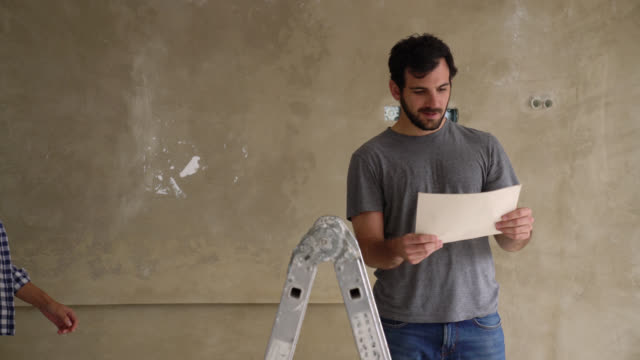 cheerful man planning a home renovation looking at a document and then female partner arrives very happy to see what he is doing - housing development stock videos & royalty-free footage