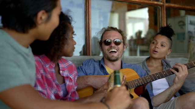 cheerful man playing guitar for friends on porch - maraca stock videos & royalty-free footage
