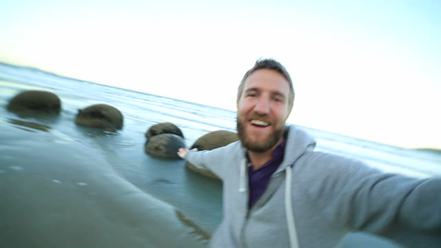 Fröhlich Mann befindet sich in der Nähe der Moeraki boulders, nimmt Selfies Porträt