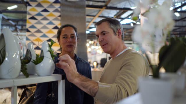 vídeos de stock, filmes e b-roll de homem alegre que fala à esposa sobre a planta no indicador de varejo em uma loja de móveis ambos que olham muito felizes - vitrine de varejo
