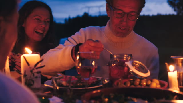 Cheerful man talking with friends while removing pickled onion rings from jar at dining table during harvest dinner party at backyard