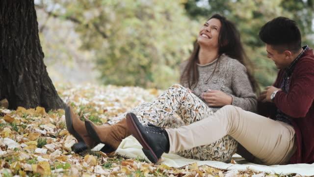 fröhlicher mensch kitzeln seine freundin während herbsttag im park und spaß mit ihr. - kitzeln stock-videos und b-roll-filmmaterial