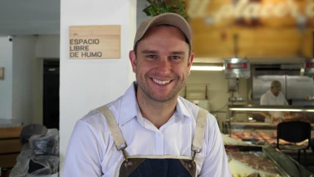 vídeos y material grabado en eventos de stock de hombre alegre que trabaja en una delicatessen mirando a la cámara sonriendo - carnicero