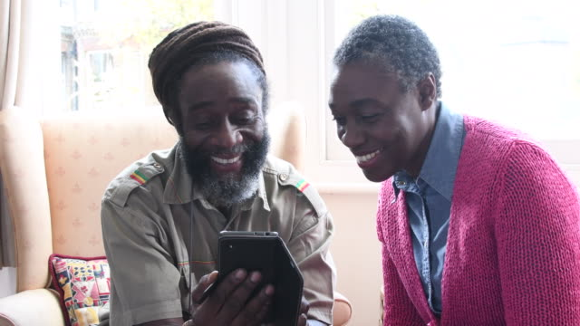 Cheerful mature African man teaching woman how to use a smartphone