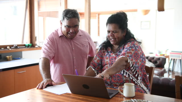cheerful mature couple using laptop at home - australian aboriginal culture stock videos and b-roll footage
