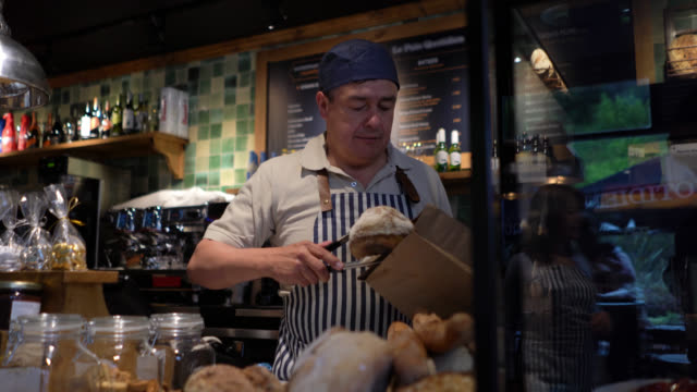 cheerful mature man working at a bakery packing bread in a paper bag for female customer very friendly and smiling - take away food stock videos & royalty-free footage