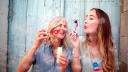 Cheerful mature mother and young daughter blowing bubbles outdoors