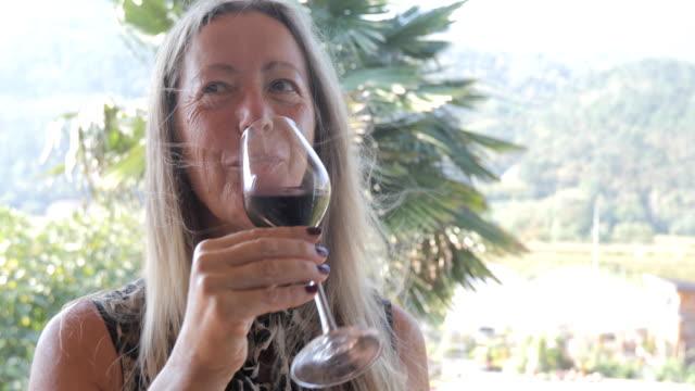 fröhliche reife frau trinken rotwein und einen toast zu machen - lang stock-videos und b-roll-filmmaterial
