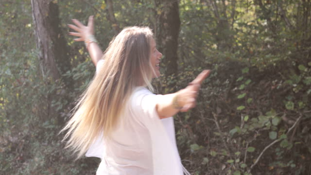 cheerful mature woman spinning around in nature - hippie stock videos & royalty-free footage