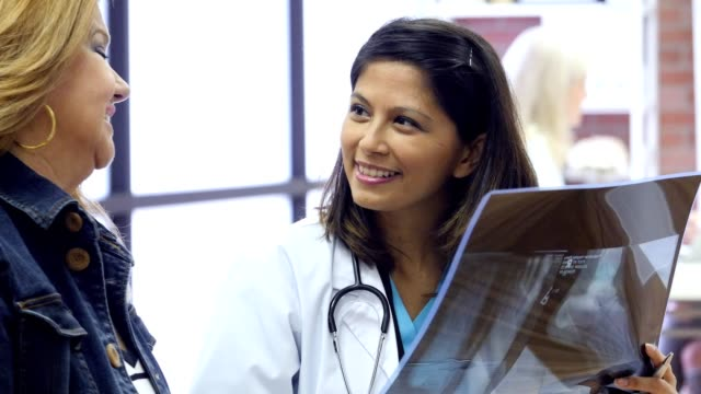 Cheerful mid adult Asian doctor talks with mature Hispanic female patient