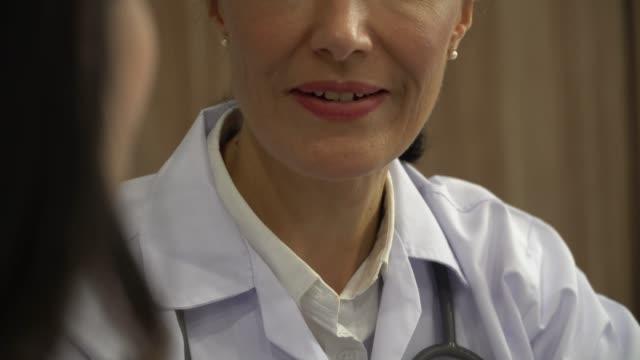 vídeos de stock e filmes b-roll de cheerful mid adult asian female doctor talks with young caucasian woman - prescription medicine