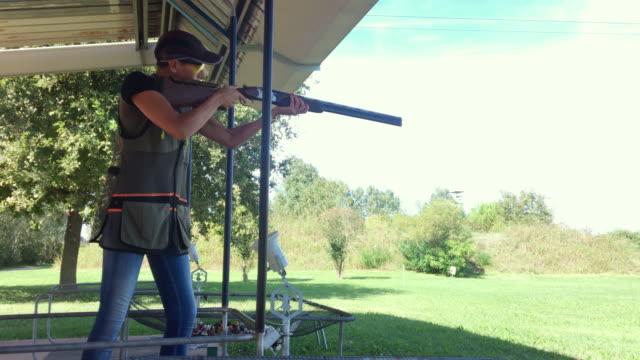 stockvideo's en b-roll-footage met vrolijke mid adult woman skeet schieten met shotgun op shooting range - jachtgeweer