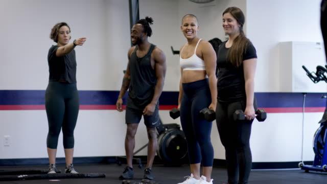 stockvideo's en b-roll-footage met een vrolijke gemengde etnische groep fitness klasse een workout samen doen - fatcamera