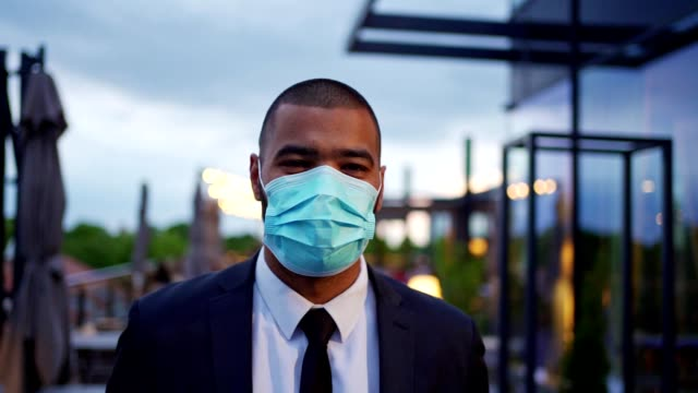 cheerful modern businessman wearing protective face mask during covid-19 pandemic - business person stock videos & royalty-free footage