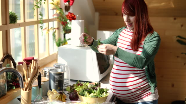 cheerful modern pregnant woman preparing healthy salad for lunch - candid stock videos & royalty-free footage
