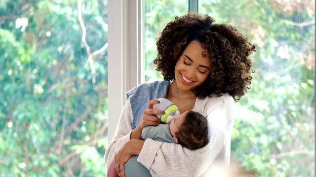 vídeos de stock e filmes b-roll de cheerful mother gives her newborn baby a bottle - alimentar