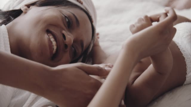 cheerful mother smiling while watching her sleepy baby - baby girls stock videos & royalty-free footage