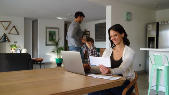 cheerful mother working on laptop looking at her family at background play together all having fun - four people stock videos & royalty-free footage
