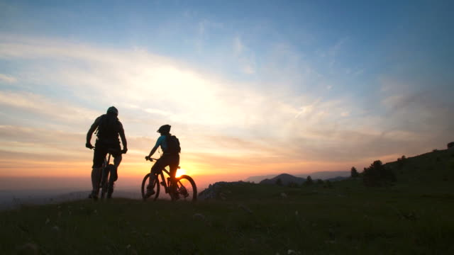 stockvideo's en b-roll-footage met hd: cheerful mtb cyclists on the top of mountain - back lit