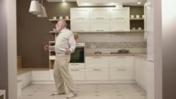 Cheerful Old Man Dancing In The Kitchen
