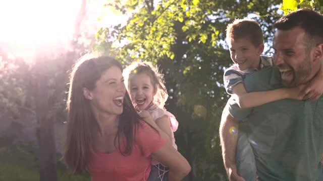 vídeos de stock, filmes e b-roll de pais alegres dando aos filhos carona na natureza. - grama