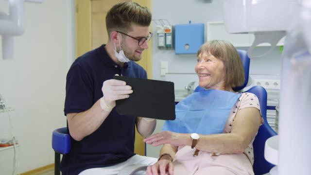 vídeos de stock e filmes b-roll de cheerful patient and dentist discussing in clinic - dentista