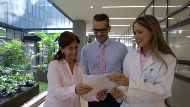 vídeos de stock, filmes e b-roll de paciente alegre que fala ao gerente do doutor e do hospital ao andar através dos hospitais - quadro médico