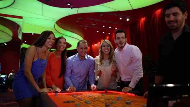 Cheerful people gambling on the roulette waiting for the wheel to stop