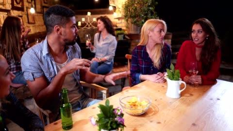 vídeos y material grabado en eventos de stock de gente alegre sentada en un bar disfrutando de su tiempo hablando - cotilleo