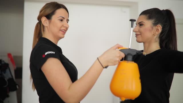 cheerful personal trainer and young woman - body abbigliamento sportivo video stock e b–roll