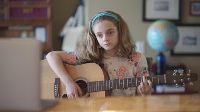 vidéos et rushes de cheerful pre-teen girl learns how to play the guitar via video call - guitare
