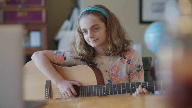 cheerful pre-teen girl practices playing the guitar while taking online lessons via video call - guitar stock videos & royalty-free footage
