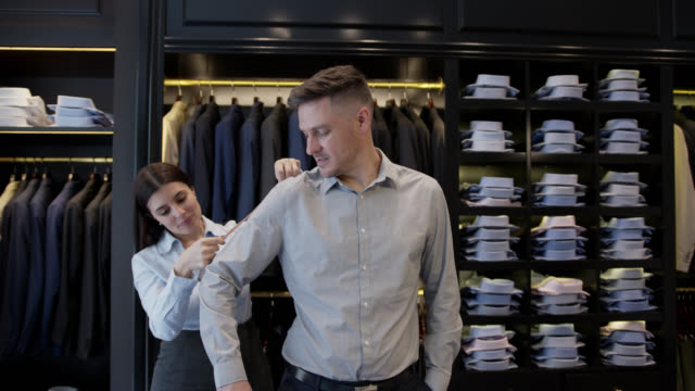 cheerful sales woman measuring the length of the arm of male customer to tailor a suite at a clothing store - tuxedo stock videos & royalty-free footage