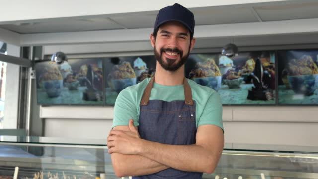 vídeos y material grabado en eventos de stock de vendedor alegre en la heladería - helado de vainilla