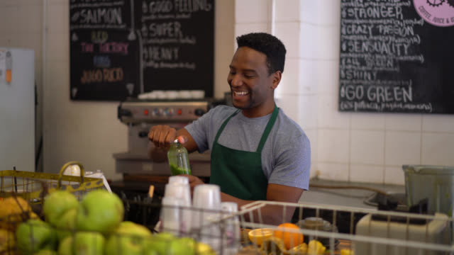 cheerful salesman serving a green juice in a bottle and then mixing it very playful and giving it to an unrecognizable customer - salesman stock videos & royalty-free footage