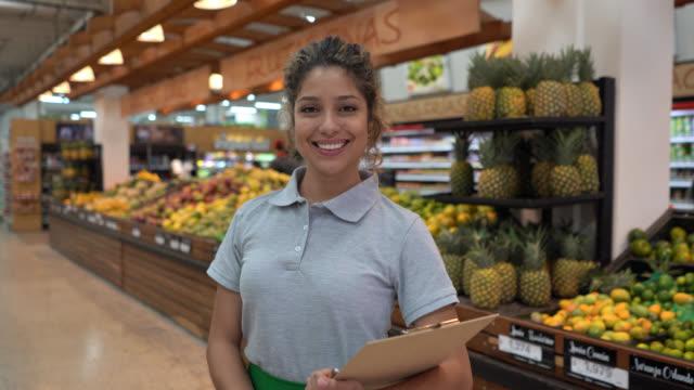 vídeos de stock e filmes b-roll de cheerful saleswoman at a megastore holding a clipboard and facing camera smiling - américa latina