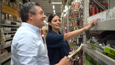 vidéos et rushes de vendeuse gaie aidant le client masculin à une quincaillerie - magasin