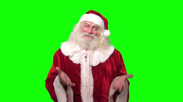 陽気なサンタクロースは、クロマキーグリーンの画面の背景の前で話し、笑顔でカメラを見て - クリスマスカード点の映像素材/bロール