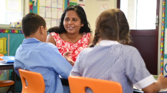 cheerful school teacher talking to boy and girl in classroom - aboriginal australian ethnicity stock videos & royalty-free footage