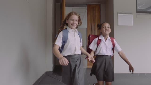 cheerful schoolgirls running in corridor - uniform stock videos & royalty-free footage