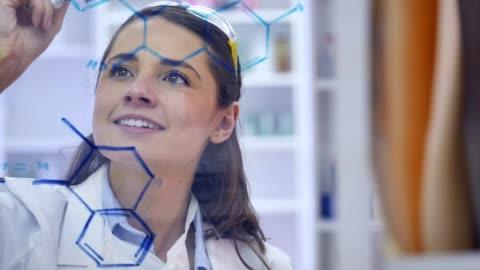 vídeos y material grabado en eventos de stock de sonrisas alegres científico con confianza mientras dibujo estructura molecular - fórmula química