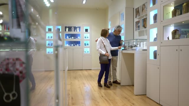 cheerful senior couple at a jewellery store looking at the different retail displays while talking - espositore per negozio video stock e b–roll