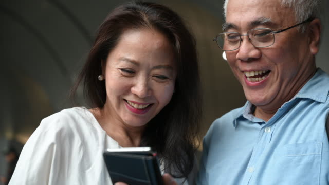 cheerful senior couple looking at smart phone together - two people stock videos & royalty-free footage