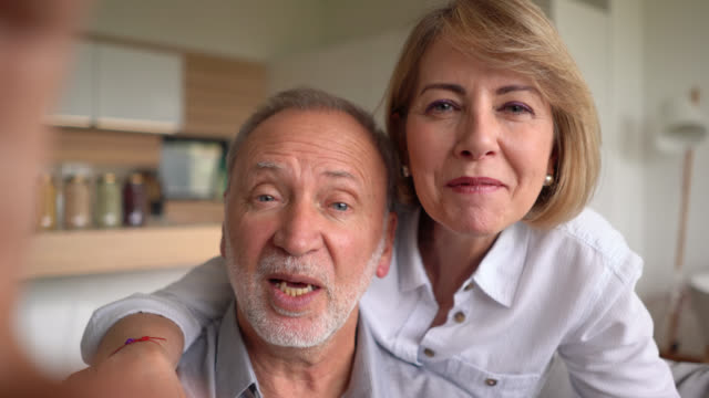 cheerful senior couple on a video conference saying hello facing camera smiling - zoom stock videos & royalty-free footage
